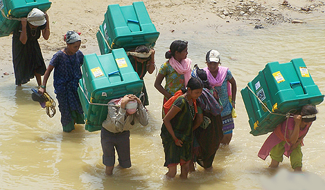 Indonesian disaster victims transport ShelterBoxes from a distribution center.