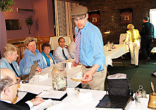 Cheesemonger Eric Paul distributes samples of his wares. In the background, Debbie and Peter Brown arrange the sampoles for him.