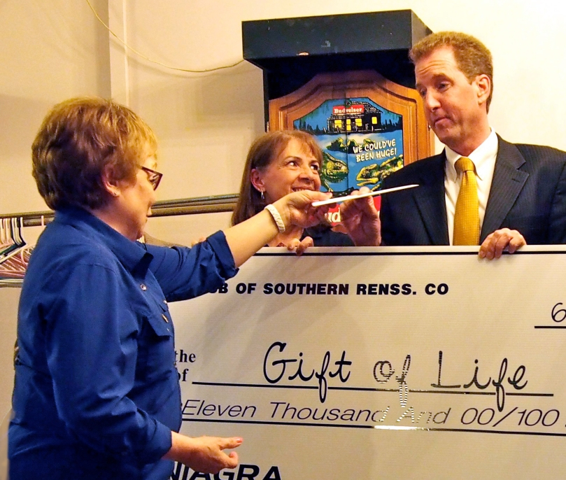 President April hands 7190 Gift of Life President Tom Burdick the club's real check for $11,000 at Thursday's dinner meeting.