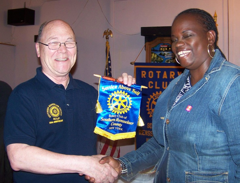 President Bill presents a club pennant to visiting Rotarian Angela Ssemukutu, presodent-elect of her club in Uganda.