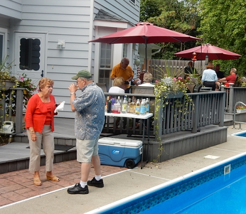 Carole Spencer and host Jim Leyhane chat by the pool.