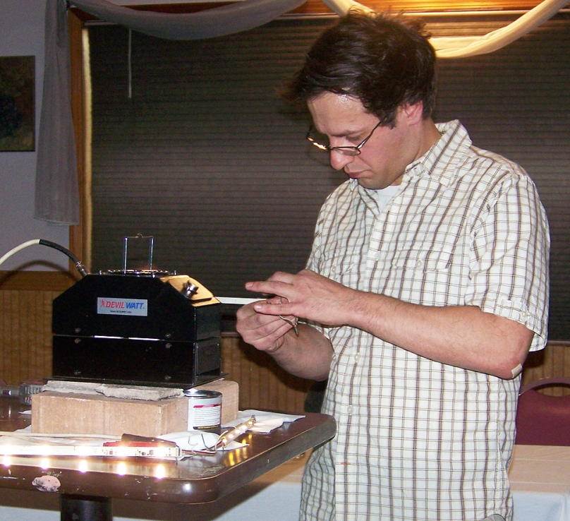Robert Parzak setting up a heat exchange device that emits energy to light a string of diodes.