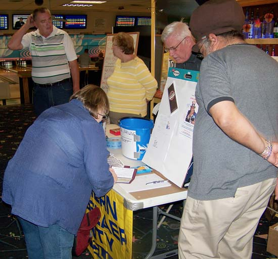 Ray Hannan and David Taylor help check-in a paticipant at the registration table. Murray Forth and Lois Hannan chat in the background.
