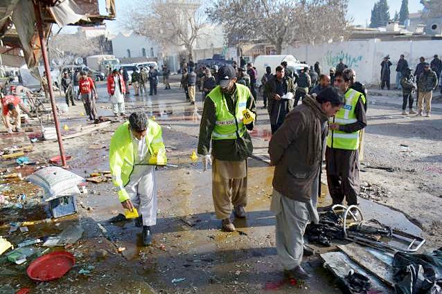 Crime scene investigators collect evidence at site of suicide-bomb attack.