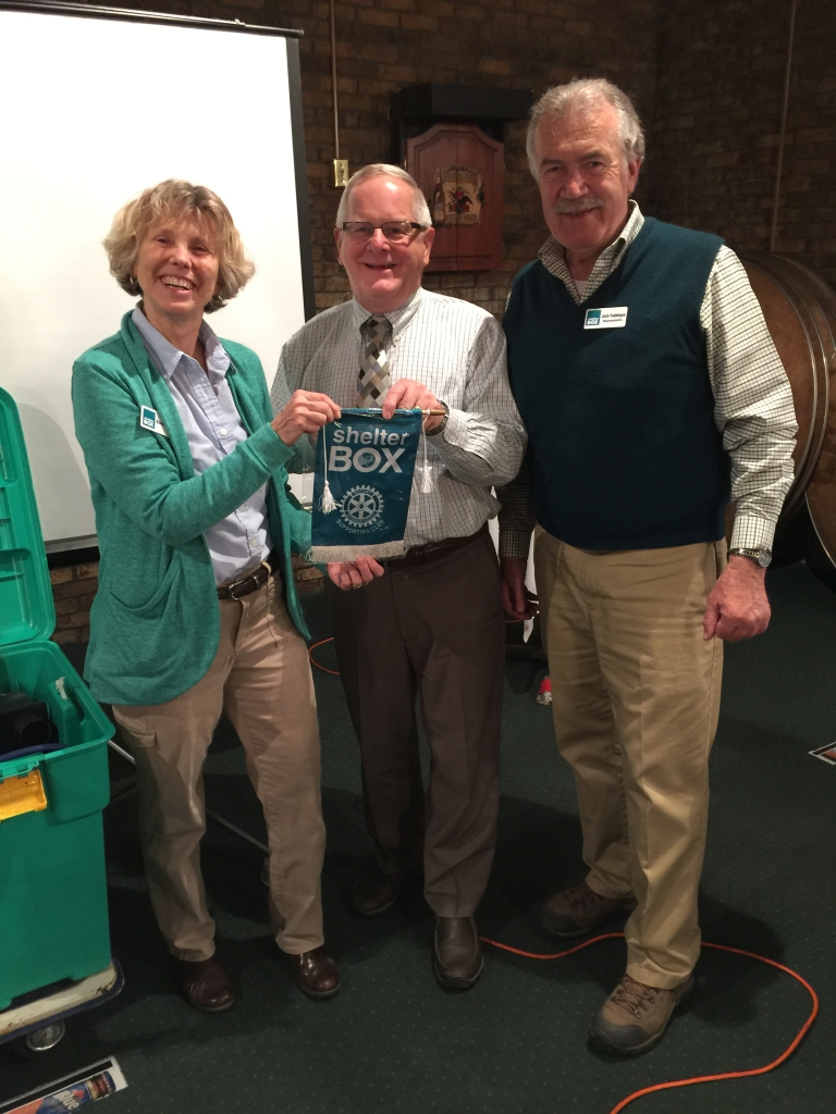 "Terry Brewer accepts the first ShelterBox ""Hero"" pennant in District 7190 from program coordinators Nancy and Jack Faddegon."