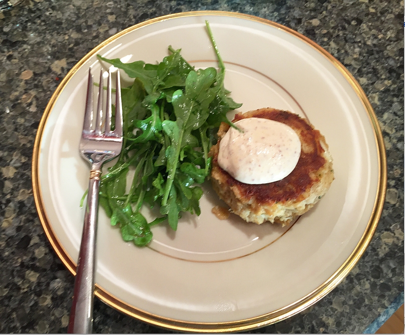 Plating a crabcake and arugula salad tasing.