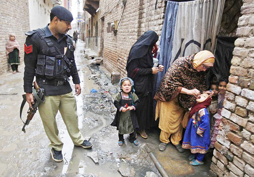 THIS IS WHAT IT TAKES -- A Pakistani health worker, accompanied by an armed security guard, administers polio vaccine to a child in Peshawar in February.